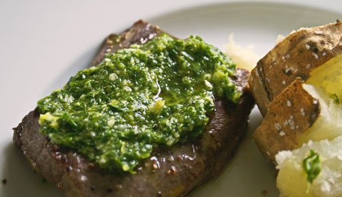 This photo shows a grilled steak on a white plate topped with green Lemon Parsley Sauce. There's also potatoes on the plate.