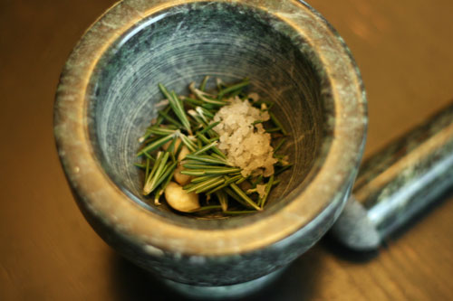 Seasonings for Lemon Rosemary Vinaigrette Recipe are shown in a mortar pestle.
