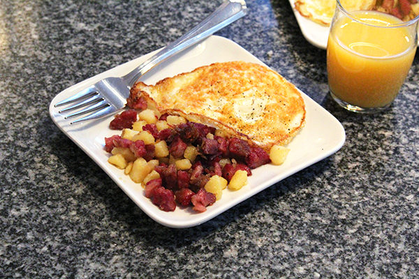 A square white plate holds corned beef hash and a fried egg. Nearby is a glass of orange juice and a second plate.