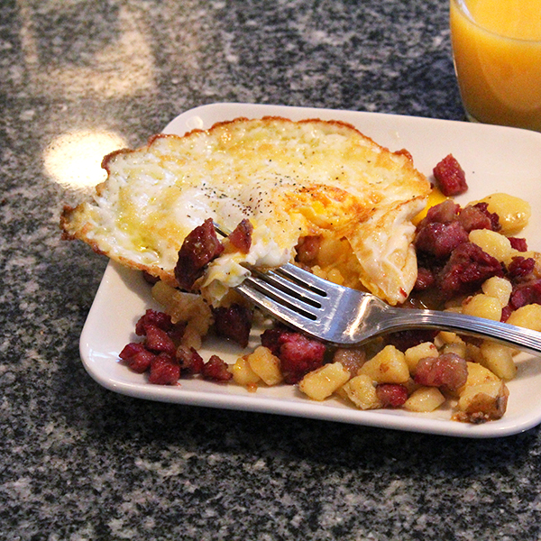 A square white plate of corned beef hash with a fried egg sits on a granite countertop with a forkful of hash resting on the plate.