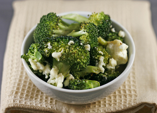 A white bowl of green roasted broccoli and white feta, both with bites of brown caramelization.