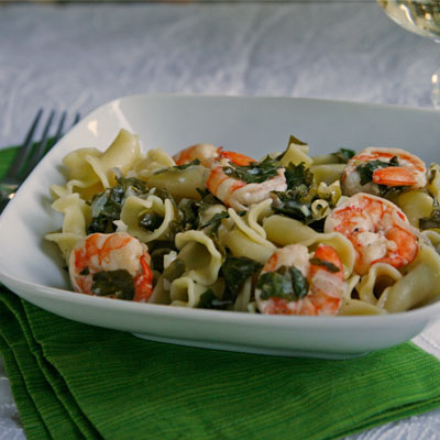 Summer Pasta with Shrimp and Kale is shown in a white bowl set on a green napkin.