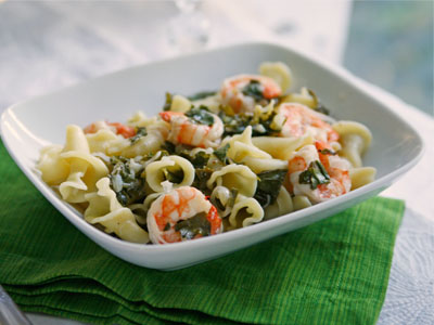 a white bowl of Summer Pasta with Shrimp and kale is set on a green napkin