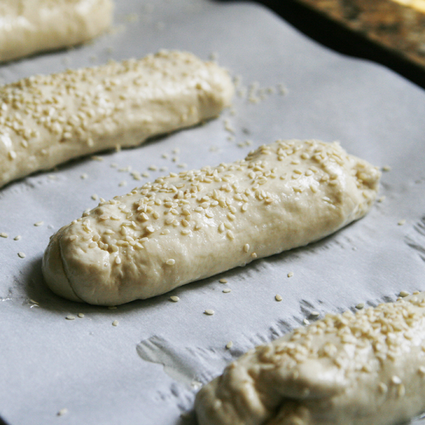 This photo shows Sesame Rolls Ready to Bake on a parchment-lined baking sheet.