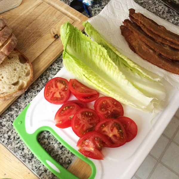 This shows the ingredients for a BLT on a white cutting board: tomatoes, lettuce and bacon. Sliced bread sits on a wooden cutting board nearby.