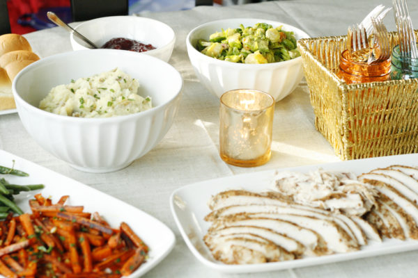 A table is set for the holiday with a smaller Thanksgiving meal that includes mashed potatoes and a salad in bowls, cranberry sauce, turkey, carrots, a tea light and cutlery.