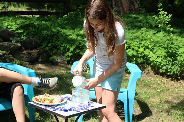 A girl pours fresh lemonade into glasses.