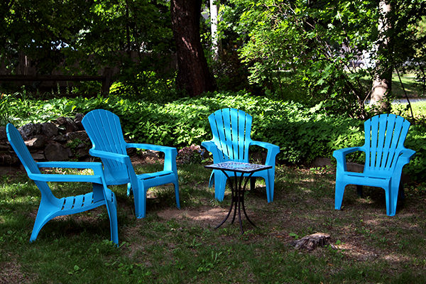 Four teal plastic chairs sit outside around a small table.