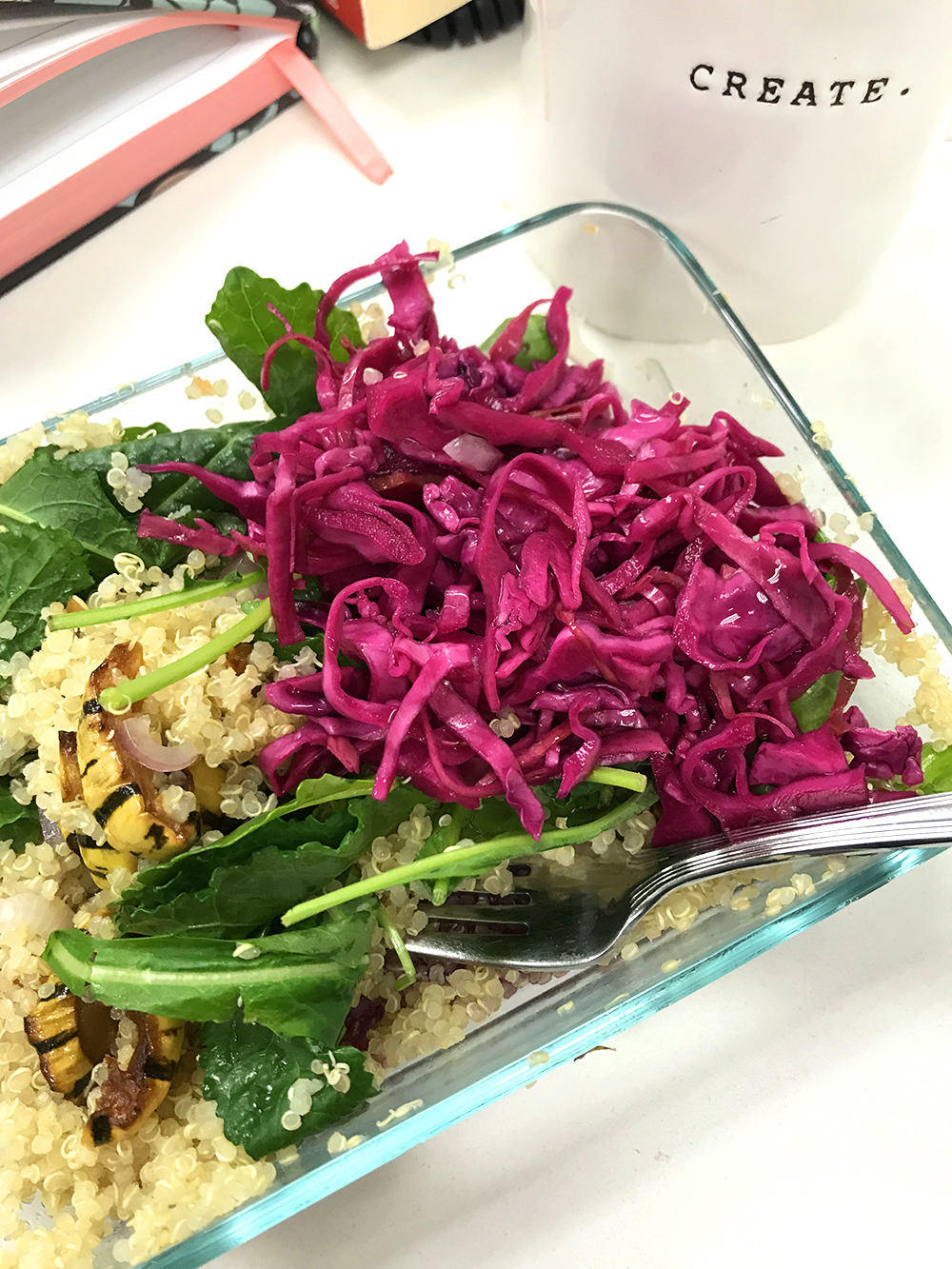 "A desk lunch featuring quinoa, arugula, roasted squash and pickled red cabbage. Nearby, a mug with the word ""create"" stamped on it."