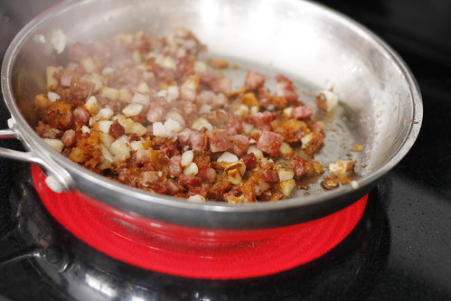 Diced corned beef and potatoes fry in a stainless steel pan on a hot burner.