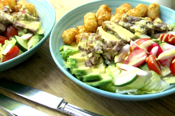 This Steak and Potato Salad recipe features avocado, radishes, tomatoes, lettuce, cucumbers, sirloin steak, tater tots and hollandaise sauce made in a blender.