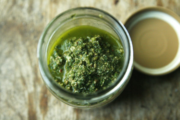 A jar of Basil Pecan Pesto is shown with the lid beside it. This can be made with fresh basil from the farmers market or your garden.