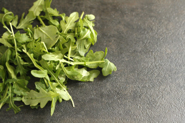 fresh baby arugula on a dark background