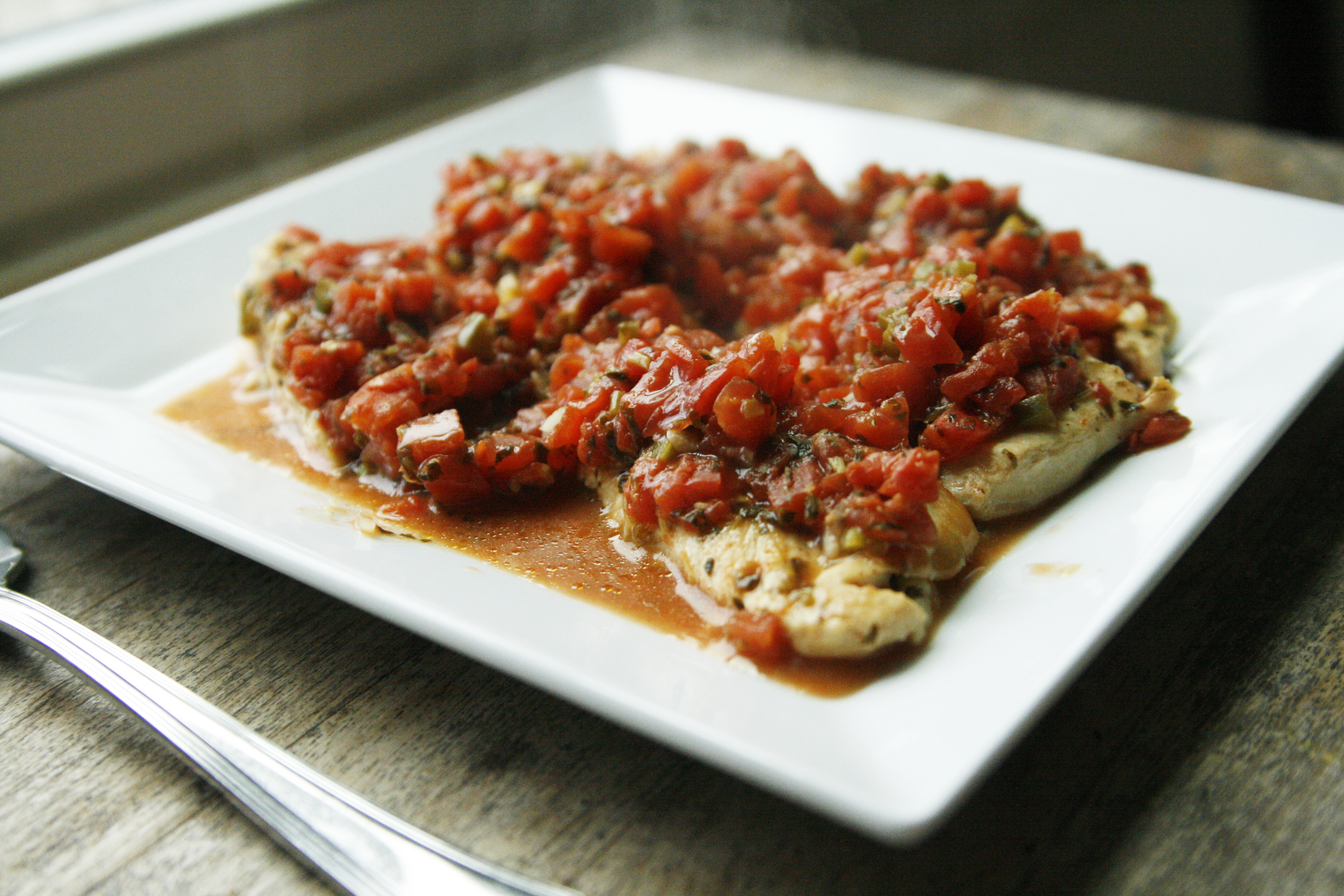 Pico De Gallo Chicken Skillet is shown on a plate. Chicken is topped with a red tomato salsa.