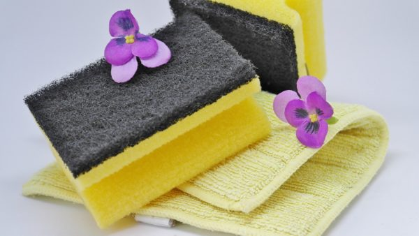 "A stack of sponges and rags with two flowers on them to signify natural cleaning. Image by <a href=""https://pixabay.com/users/RitaE-19628/?utm_source=link-attribution&utm_medium=referral&utm_campaign=image&utm_content=3254675"">RitaE</a> from <a href=""https://pixabay.com/?utm_source=link-attribution&utm_medium=referral&utm_campaign=image&utm_content=3254675"">Pixabay</a>"