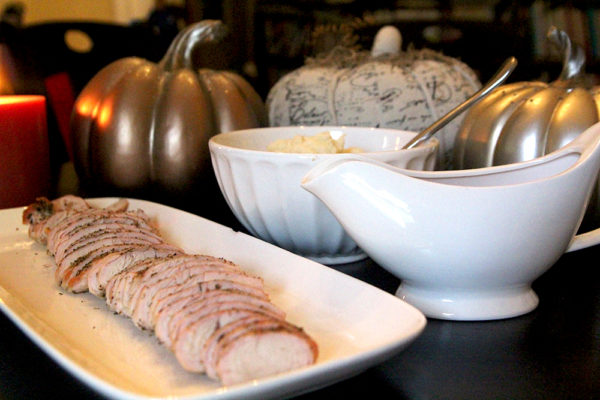This photo shows turkey on a platter surrounded by decorative pumpkins, a bowl of mashed potatoes and a pitcher of gravy. It's a small Thanksgiving meal!