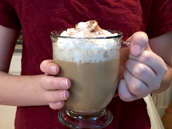 how to make eggnog coffee - Hands holding a coffee mug with a coffee drink topped with whipped cream