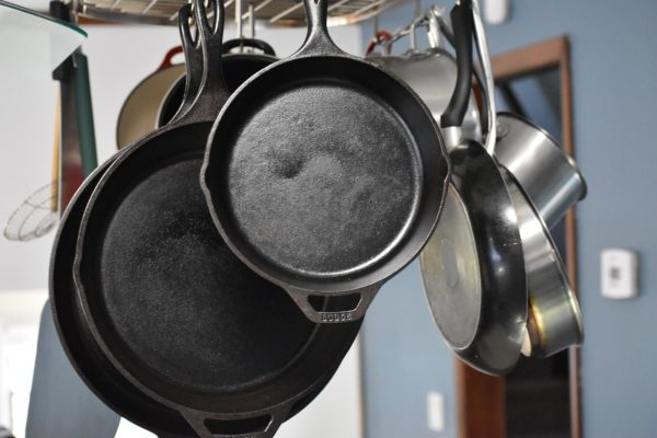 """Cast iron pans hanging from a rack - Image by <a href=""""https://pixabay.com/users/Ernest_Roy-1284978/?utm_source=link-attribution&utm_medium=referral&utm_campaign=image&utm_content=4229579"""">Ernest_Roy</a> from <a href=""""https://pixabay.com/?utm_source=link-attribution&utm_medium=referral&utm_campaign=image&utm_content=4229579"""">Pixabay</a>"""