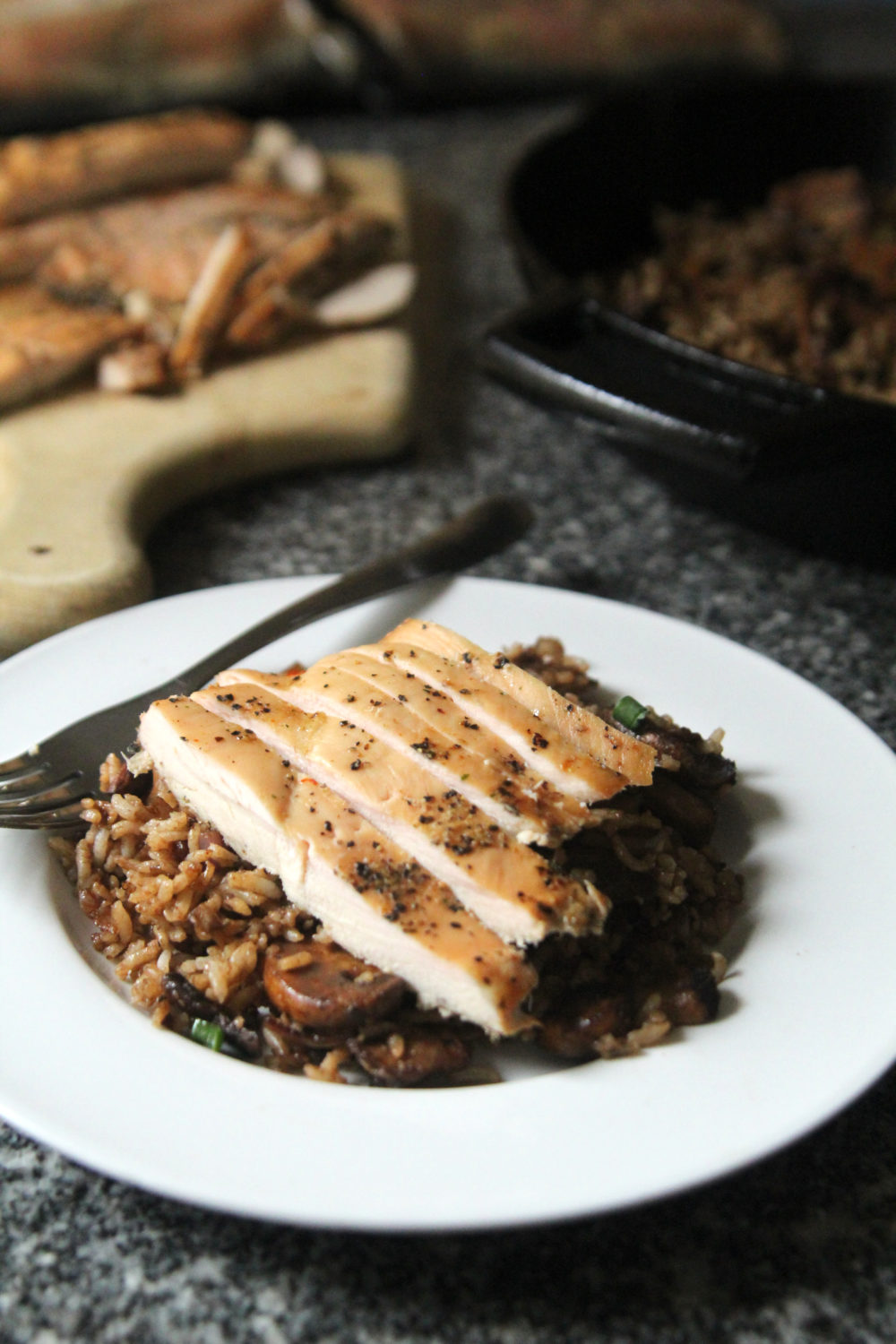 A white plate of Balsamic Mushroom Rice with Shallots topped with chicken