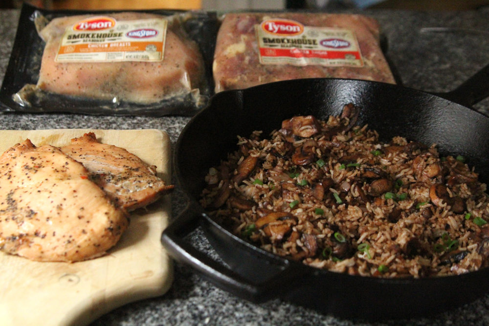 Cooked chicken breasts, a skillet of rice with mushrooms and shallots, two packages of marinated chicken