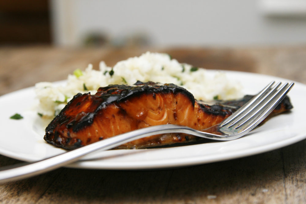 Broiled Teriyaki Salmon with Spring Onion Rice shown on a white plate. The salmon is dark in spots.
