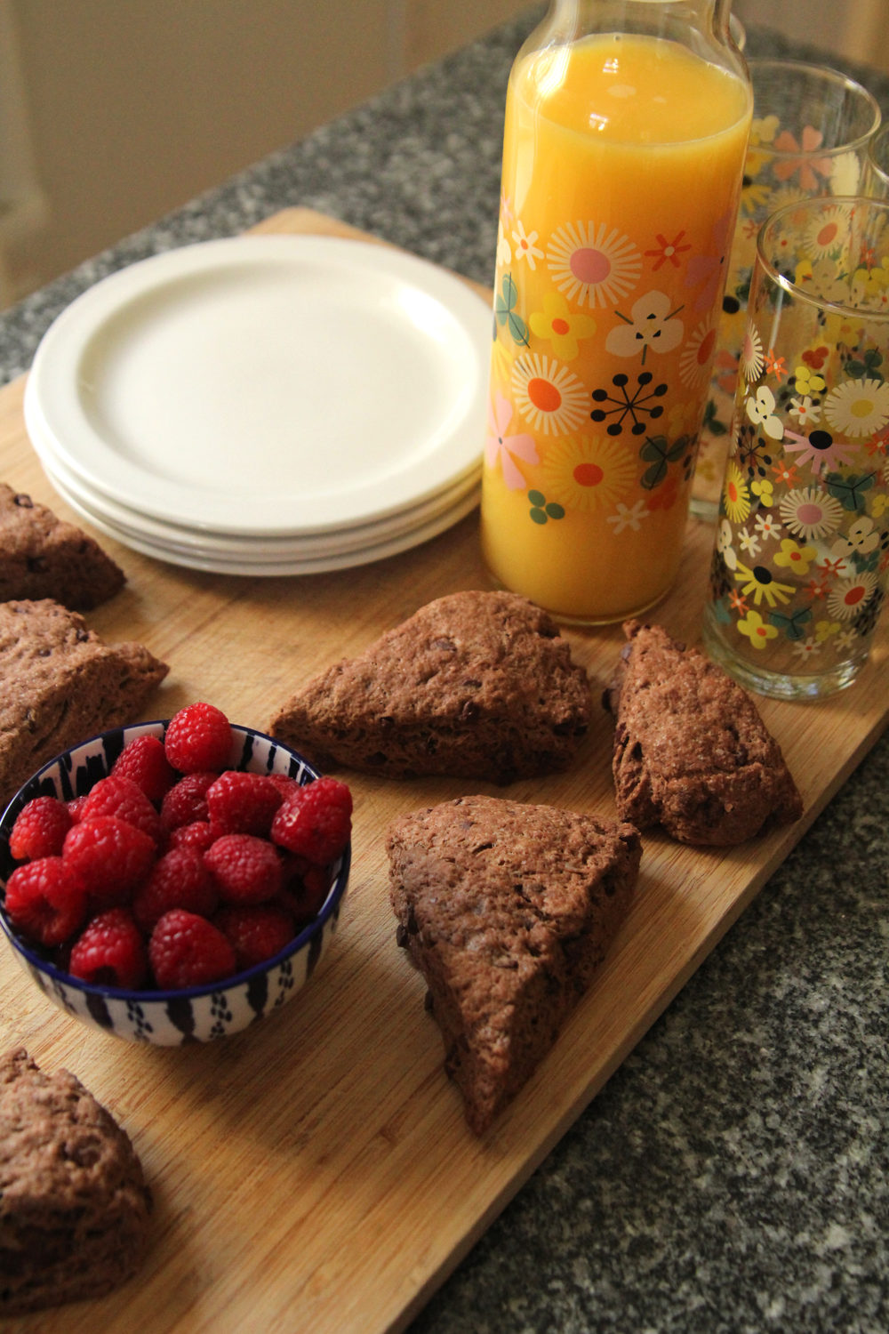 double chocolate scones recipe shown with a glass pitcher of orange juice, a bowl of raspberries and a stock of white plates on a wooden cutting board.