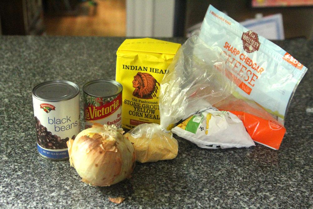 Ingredients for Black Bean Corn Enchilada Pie are shown on a gray granite countertop.