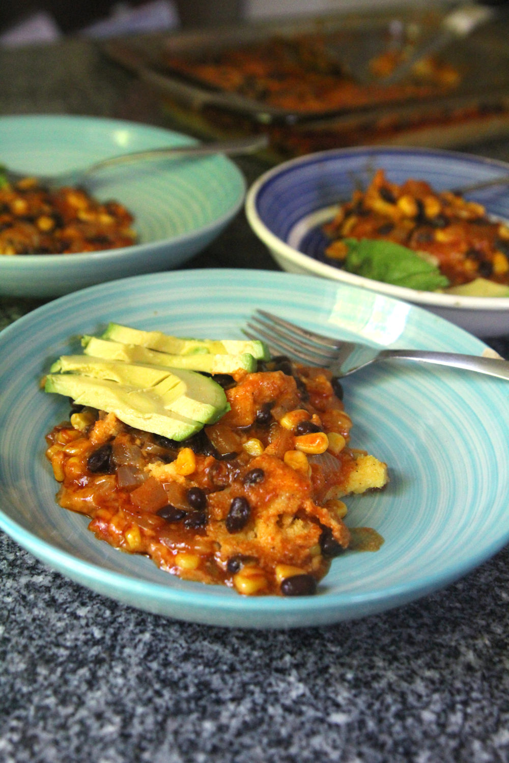 Black Bean Corn Enchilada Pie is shown in three bowls with slices of avocado.