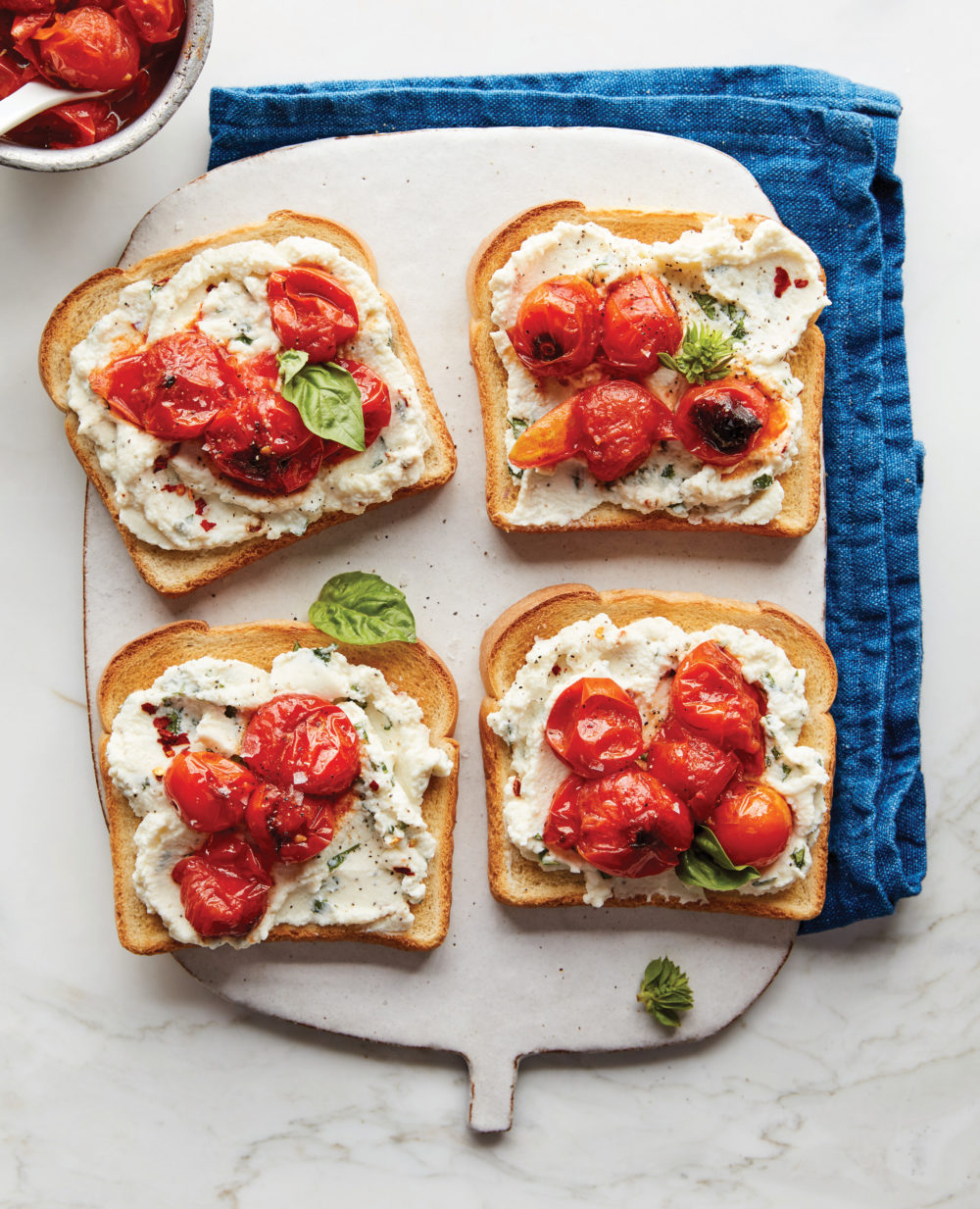 Tomato Ricotta Toast with Basil shown on a white plate over a turquoise napkin.