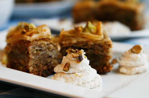 A closeup of cinnamon whipped cream on a white plate with Pistachio Walnut Honey Baklava in the background.