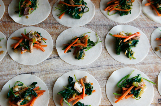 Dumpling wrappers topped with green and orange veggies sit on a wood cutting board.