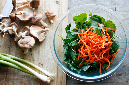 A bowl of kale and carrots sit near a cutting board of shiitake mushrooms and scallions.