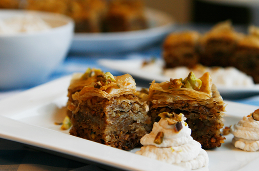 Pistachio Walnut Honey Baklava is shown on a white plate with a swirl of cinnamon whipped cream.