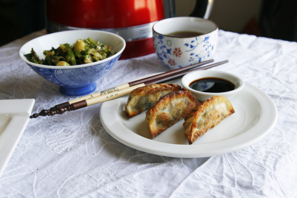 A white plate with Kale and Mushroom Gyoza and a small bowl of soy sauce sit with chopsticks. A tea cup with tea and a bowl with green vegetables sits nearby.