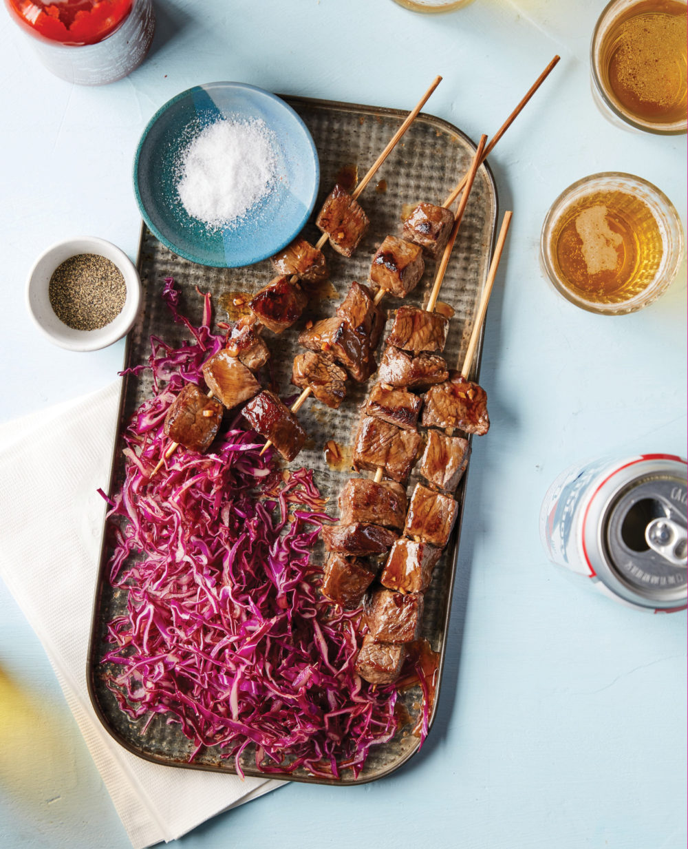 A tray holds Hoisin Beef Skewers with Gingery Red Cabbage Slaw.