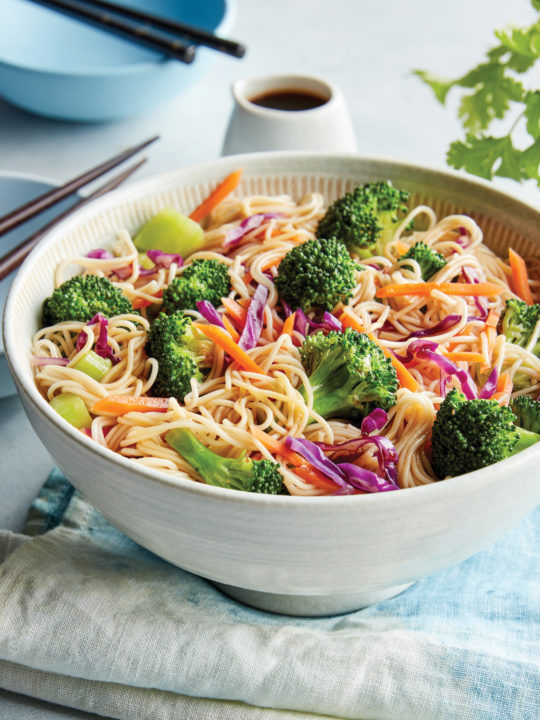 A white bowl has noodles with broccoli, red cabbage and other vegetables in it.