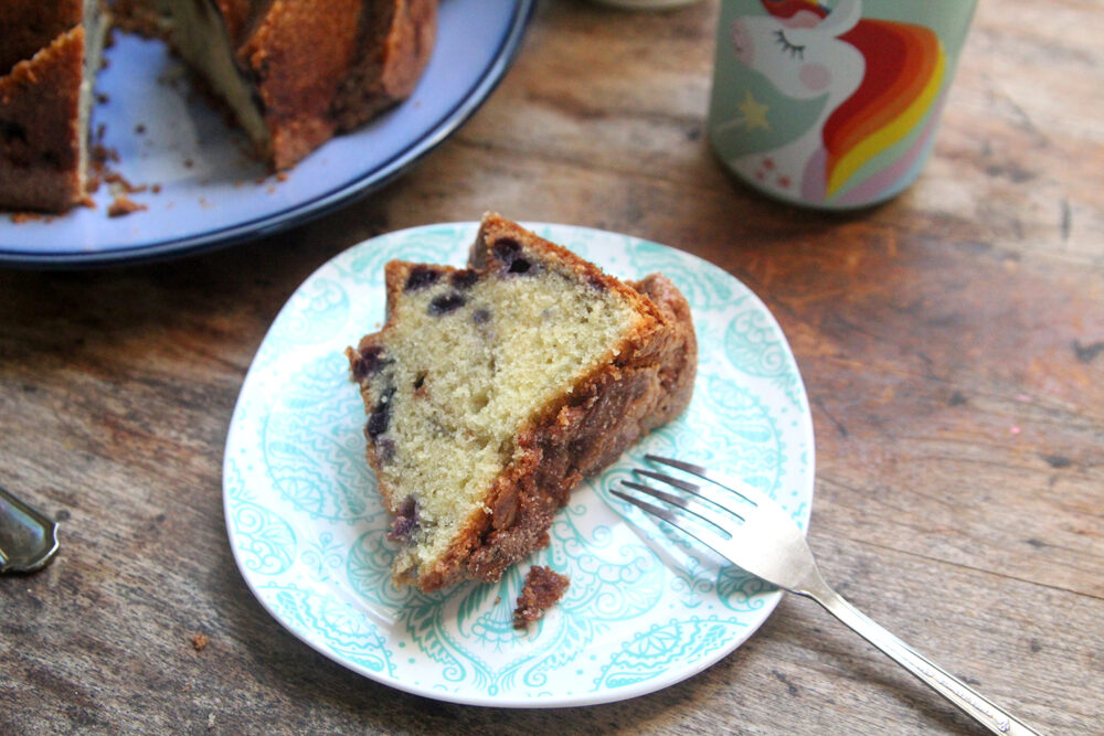 A slice of wild blueberry pound cake is on a plate with a fork. The rest of the cake and a unicorn measuring cup sit nearby.