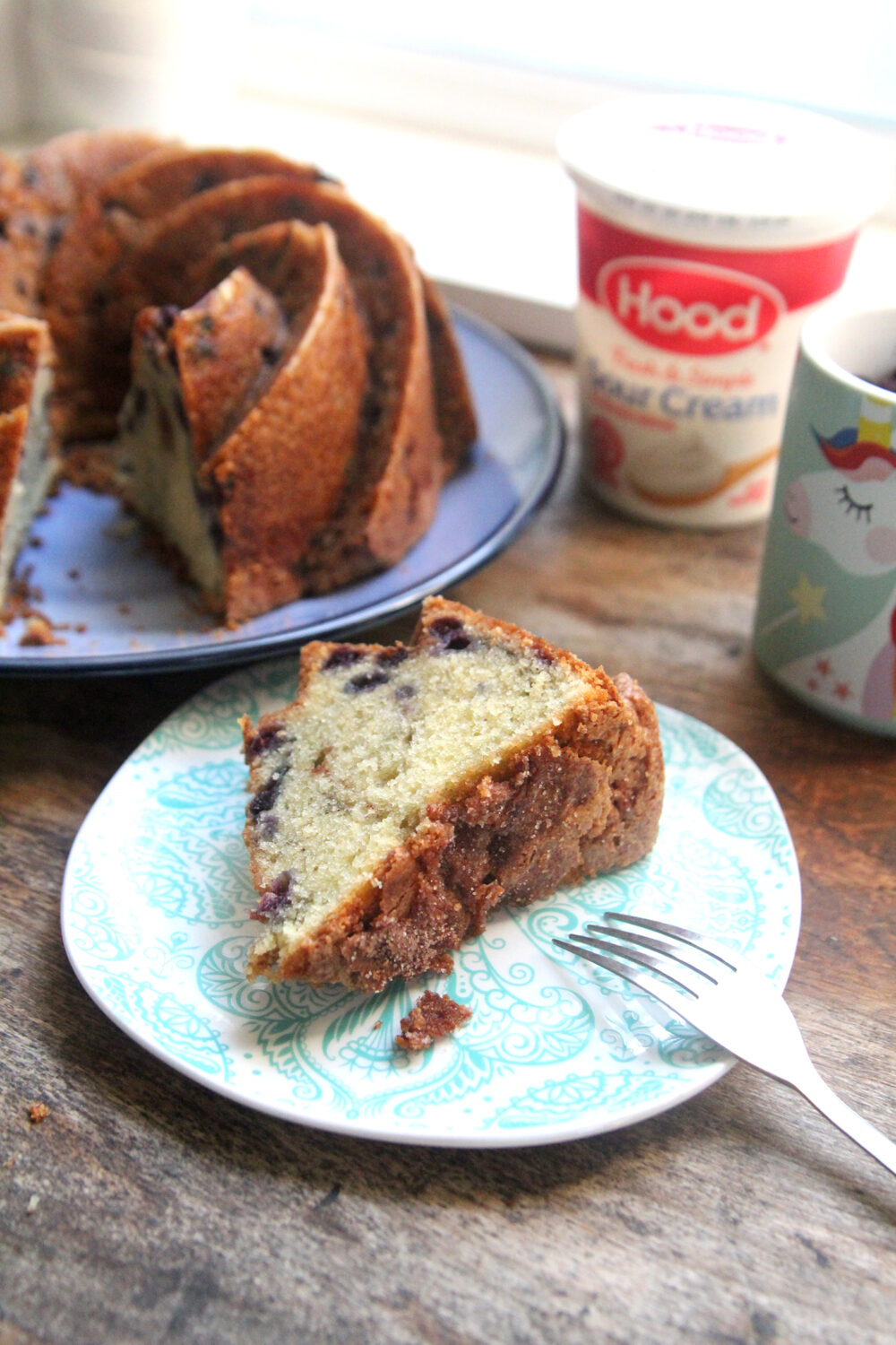 A slice of wild blueberry poundcake is on a small plate. The rest of the cake is on a big plate. Hood Sour Cream and a unicorn measuring cup sit nearby.