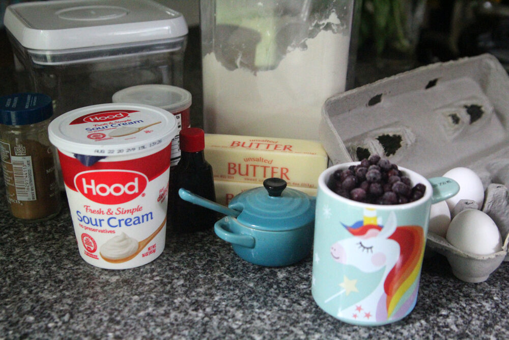 ingredients for wild blueberry pound cake sit on a granite countertop.