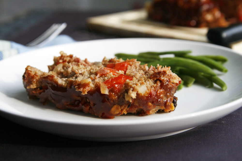 A slice of Barbecue Turkey Bacon Meatloaf is shown on a plate with green beans.
