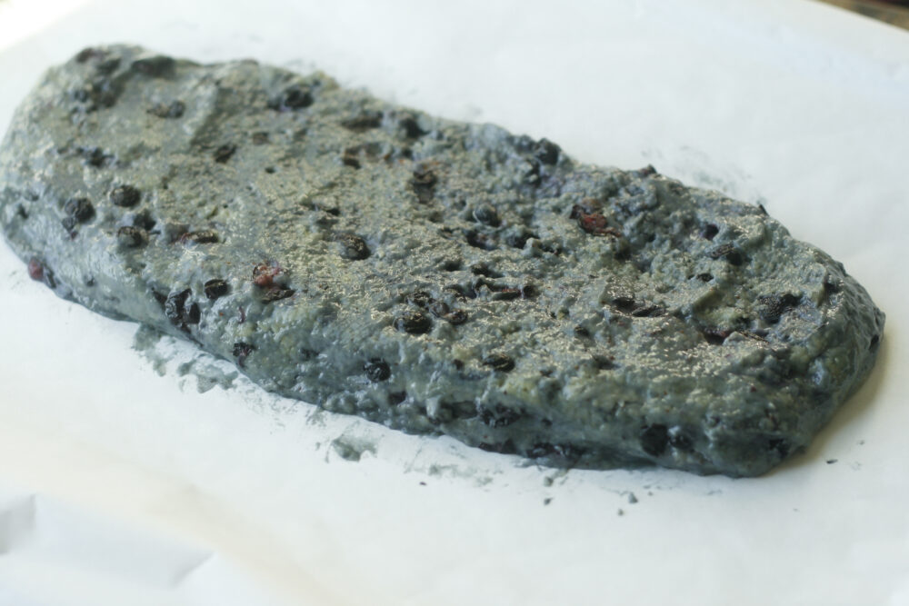 A wet log of dough is shown on parchment paper.