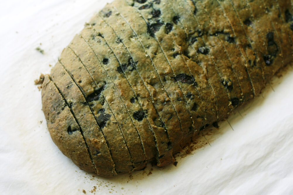 A browned loaf with dots of blueberries is shown sliced on parchment paper.