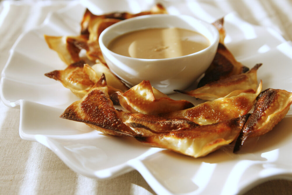 baked peanut chicken wontons are shown on a white plate with a bowl of peanut dipping sauce. The image has  sunlight lines across it from blinds.