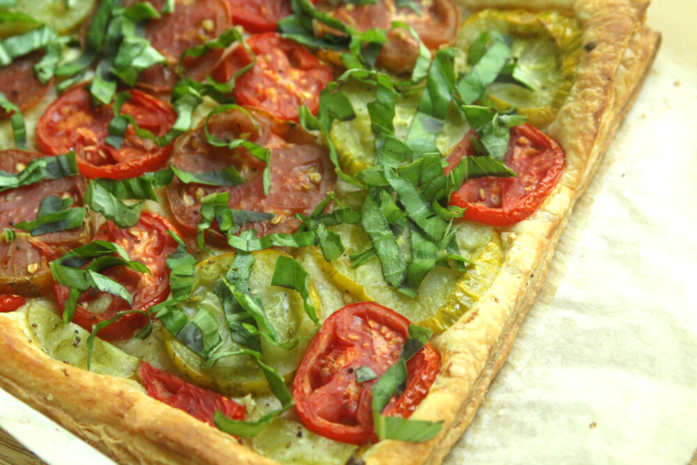 A browned puff pastry topped with red and green tomatoes and fresh basil sits on a sheet of parchment pepper.