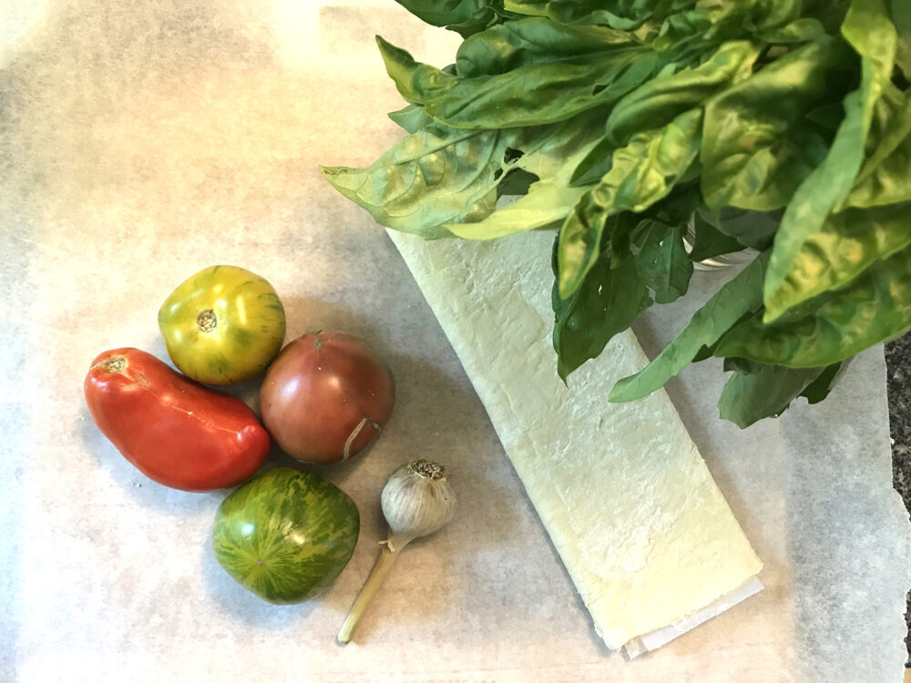 Ingredients for a Tomato Basil Tart are shown: puff pastry, tomatoes, garlic and basil