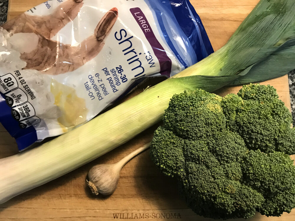 Ingredients are shown on a wooden cutting board: frozen shrimp, a leek, garlic and broccoli.