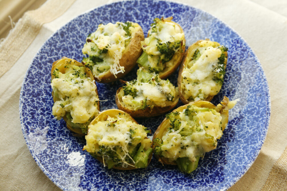 Broccoli and cheddar filled potatoes on a blue and white plate.