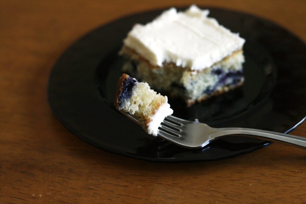 A bite of Blueberry Cake with Fluffy Vanilla Frosting is on a fork. Nearby the slice of cake sits on a purple glass plate on a wooden table.