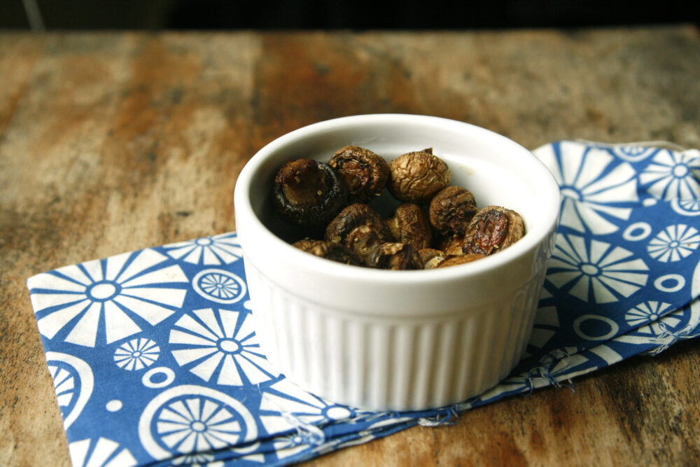 A white bowl of Herbed Roasted Mushrooms sits on a blue and white napkin on a wood table.