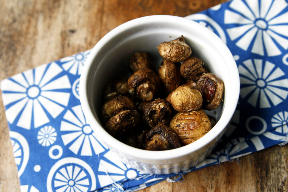 A white bowl of browned Herbed Roasted Mushrooms sits on a blue and white napkin on a wooden table.
